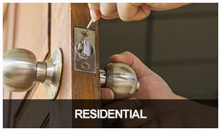 Image of a locksmith installing a lockset on a residential front door.