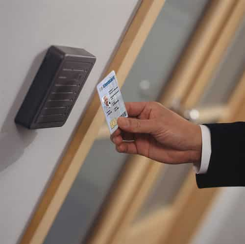 Image of a man waving a card key in front of a commercial access control card reader
